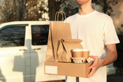 Сourier holds blank box, coffee cups and paper packages against car. Delivery