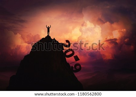 2019 overcome as a businessman lift hands up on the top of mountain reaching the finish flag. New year celebrate win and success over sunset background. Goal achievement symbol.