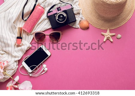 Overhead of essentials for modern student, teenager, woman. Top view of female fashion beach  accessories,straw hat, mobile phone with earphones, lipstick and body cream on bright pink background.