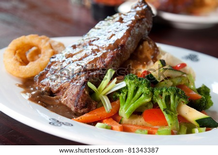 10 oz. New York Striploin Angus steak topped with Irish whiskey gravy, sauteed mushrooms and onion rings. Served with fresh vegetables and mashed potatoes. Focus on the front of the steak.