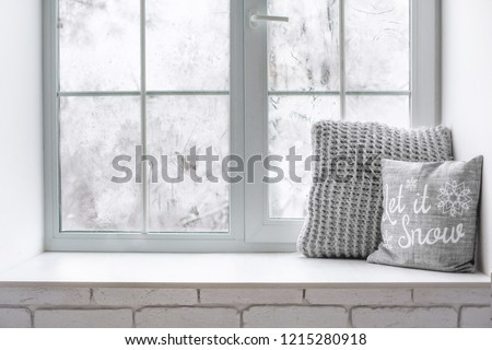 Сozy and frost winter still life:  hot tea or coffee  warm woolen knitting decoration on windowsill against snow landscape from outside. - Shutterstock ID 1215280918