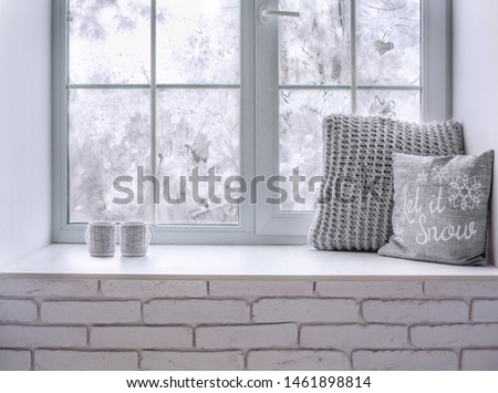 Сozy and frost winter still life:  hot tea or coffee  warm woolen knitting decoration on windowsill against snow landscape from outside.