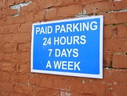 'Paid Parking, 24 Hours, 7 Days a Week' outdoor car park sign outside Drogheda train station,