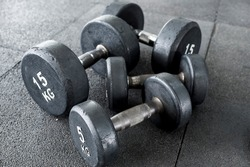 2 pairs of dumbbells cluttered on the floor of a gym. Pyramid training concept.