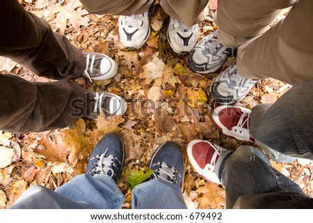 5 pairs of legs and sneakers standing in a circle in fallen leaves