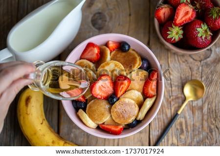 Pancake porridge, mini pancakes in a bowl with maple syrup. Dutch mini pancakes are called strawberry potato pancakes. Syrup is poured onto mini pancakes with strawberries and blueberries.