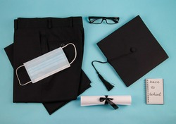 Pants, mask , graduation cap, glasses, certificate and notebook on a blue background, top view close-up.