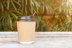 Paper cup with a lid for coffee to go on wood table,Coffee take away is on the table nature blackground,There is space for text in the background