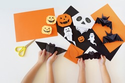 Paper toys of origami for Halloween. Hands of kids. Lesson of origami. Preparation for a holiday.