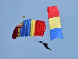 Parachute jumper. Romanian parachutist holding the Romanian flag in his hand.