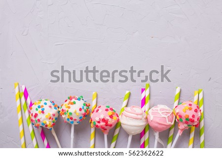 Party background. Colorful cake pops and paper straws on  grey   background. Selective focus. Place for text.