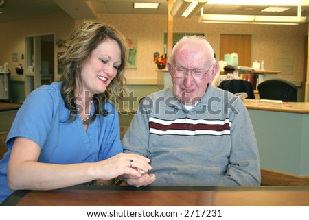 """Passing Meds"" A nurse and a nursing home resident laugh together while meds are passed out."