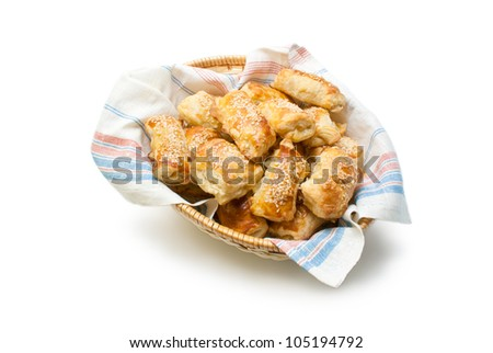 Patties. Freshly baked patties from puff pastry filled with cheese sprinkled with sesame seeds arranged in a wicker basket  isolated on white background.