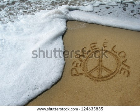 Peace & Love symbol handwritten in the sand