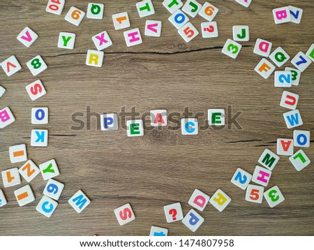 """""""Peace"""" written with colorful letters on wooden background. There are colorful scattered letters around. #1474807958"""