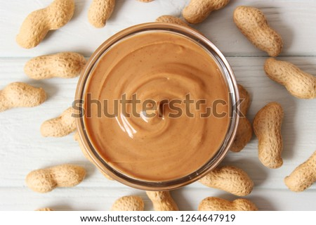 peanut butter and peanut beans on wooden background