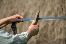 Peasant sharpening his scythe to cut the grass,banat-romania