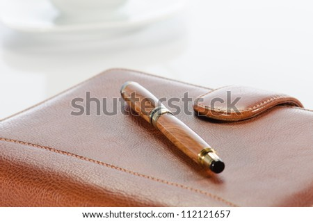 Pen and  leather notebook against a  white background - stock photo