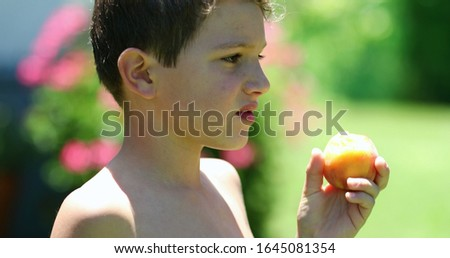 Pensive young boy eating healthy fruit snack outside in backyard. Contemplative child eats peach