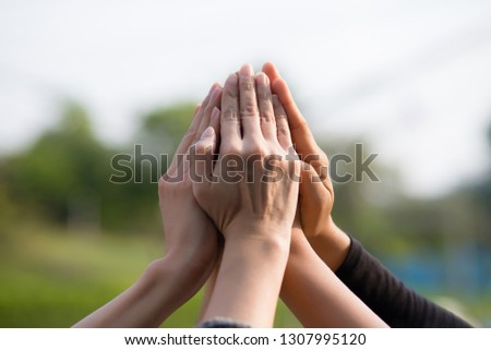 5 people are laying their hands together in the daytime in Bangkok, Thailand. Concept, unity and collaboration