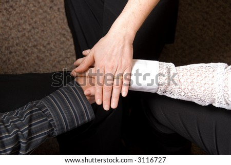 3 people clasping hands in a deal done