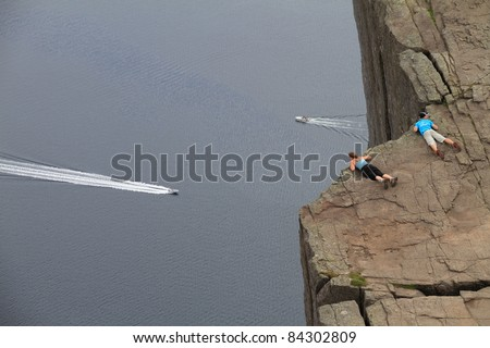 2 people looking over the edge of Pulpit Rock in Norway. Lysefjorden is in the background.