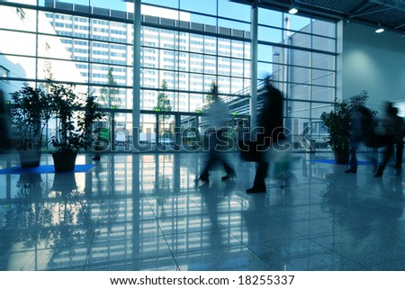 People moving in glass corridor