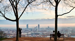 2 people sitting on a bench admiring a wonderful sunrise over the city of Lyon in France with a tourist taking picture of the view