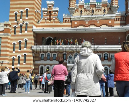 """People watch, take pictures and shoot a project (moving sculpture composition) """"Jesus on a donkey and twelve apostles"""" on the square."""