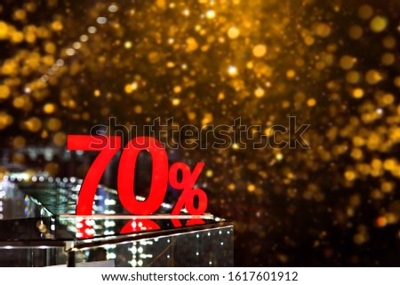 70 percent discount with golden bokeh background. Discounts in the shopping center. Seasonal sale, black friday. Red label.