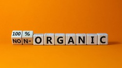 100 percent organic symbol. Fliped wooden cubes and changed words non-organic to 100 percent organic. Beautiful orange background, copy space. Business, healthy lifestyle 100 percent organic concept.