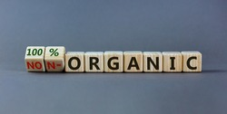 100 percent organic symbol. Fliped wooden cubes and changed words non-organic to 100 percent organic. Beautiful grey background, copy space. Business, healthy lifestyle 100 percent organic concept.