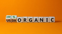 100 percent organic symbol. Fliped wooden cubes and changed words USDA organic to 100 percent organic. Beautiful orange background, copy space. Business, healthy lifestyle 100 percent organic concept.