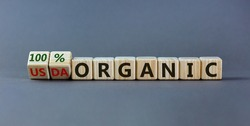 100 percent organic symbol. Fliped wooden cubes and changed words USDA organic to 100 percent organic. Beautiful grey background, copy space. Business, healthy lifestyle 100 percent organic concept.