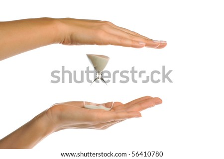 perfect female hand and fingers holding sand hourglass timer against white background