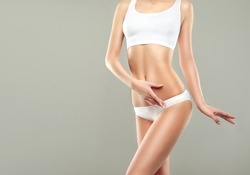 Perfect slim toned young body of the girl . An example of sports , fitness or plastic surgery and aesthetic cosmetology.