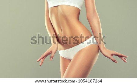 Perfect slim toned young body of the girl . An example of sports , fitness or plastic surgery and aesthetic cosmetology.  #1054187264