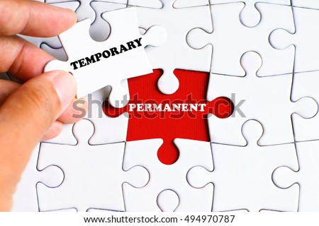 'PERMANENT' word on missing puzzle with a hand hold a piece of 'TEMPORARY' word puzzle want to complete it - business and finance concept ストックフォト ©