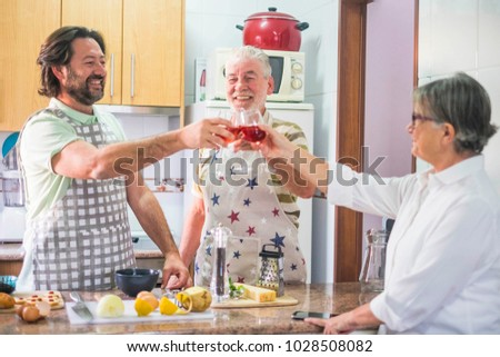 3-person family toasting with red wine while preparing dishes prepared in the home kitchen #1028508082