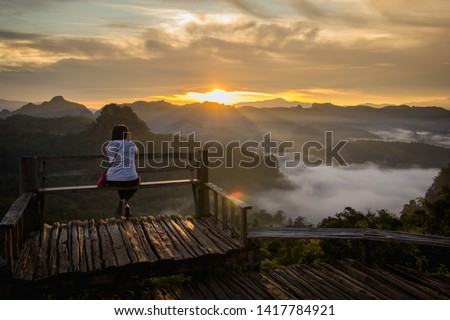 1 person woman sitting looking to viewpoint mountains and forests at the morning time ,The place is Japo Village. Pang Mapha District Mae Hong Son Province , Northern Thailand