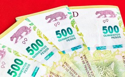 500 pesos banknotes in money close-up of argetina's currency, the Argentine peso, isolated on red background. Photo for representation of economy, finance and business.