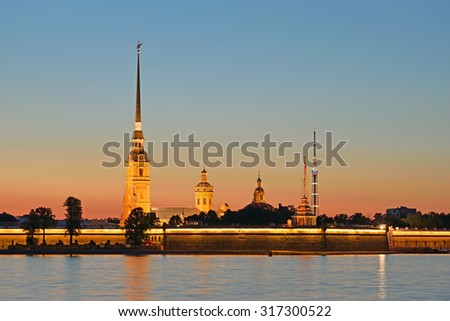 Peter and Paul fortress with the Palace promenade at sunset on a background of pure pink sky with reflection in the water of the Neva river during the white nights in St. Petersburg