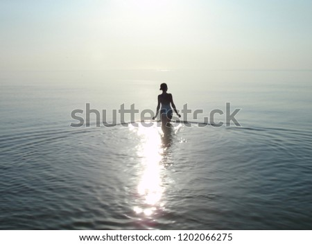 Photo of a girl from the back going into the sea against the background of quiet water merging with the sky on the horizon.