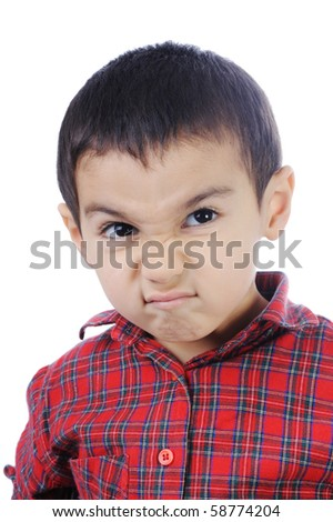 Photo of adorable young boy looking at camera, funny angry face