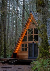 Photo of an A frame triangle shape log home in the woods, peaceful weekend getaway in nature green forest. Anniversary, romantic, relax getaway for couple or family.