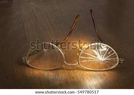 photo of broken glasses on wooden background #549780517