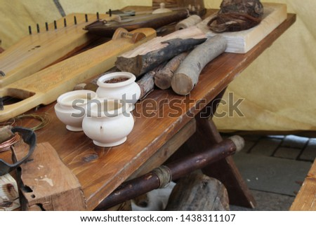 photo workshop.they make ancient musical instruments.stringed instruments.similar to the harp.on a wooden table there are pots.lies a metal wire.firewood.wood for work in the workshop. #1438311107