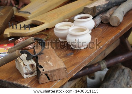 photo workshop.they make ancient musical instruments.stringed instruments.similar to the harp.on a wooden table there are pots.lies a metal wire.firewood.wood for work in the workshop. #1438311113