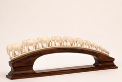 photograph of a beautiful object formed by a row of ivory elephants on a white background