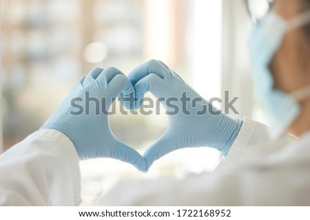 Photograph of a doctor made with his back to him who is creating a heart with his hands in which he wears gloves, we also intuit that he has a sanitary mask on his face